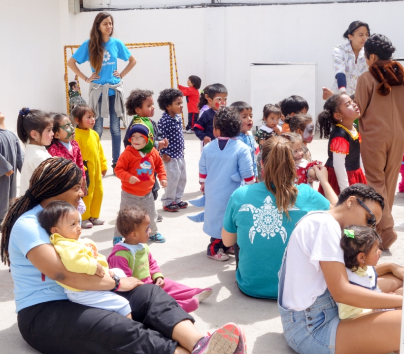 Lousiana State volunteers and teachers play with children at a daycare in Quito
