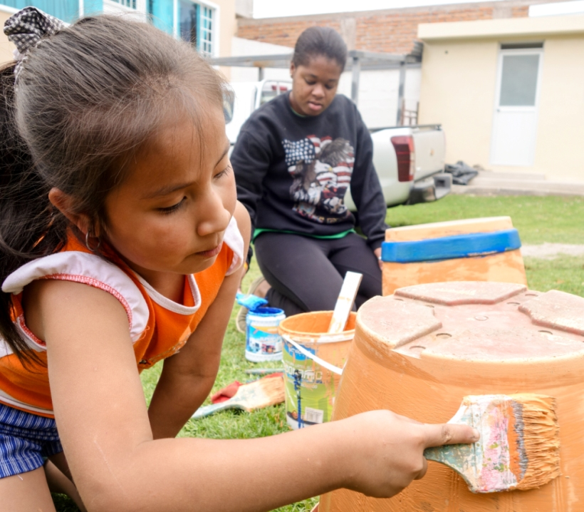 A Louisiana State volunteer and an Ecuadorian girl paint pots together at a daycare
