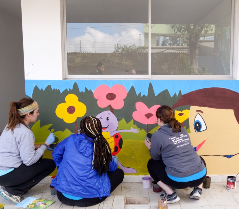 Volunteers paint a mural on a classroom wall