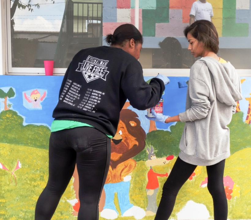 Volunteers paint a mural at a daycare in Ecuador