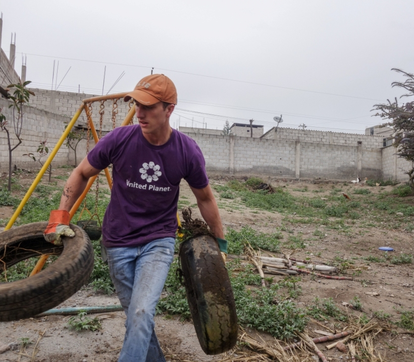 Louisiana State volunteer clearing tires out of a garden in Ecuador