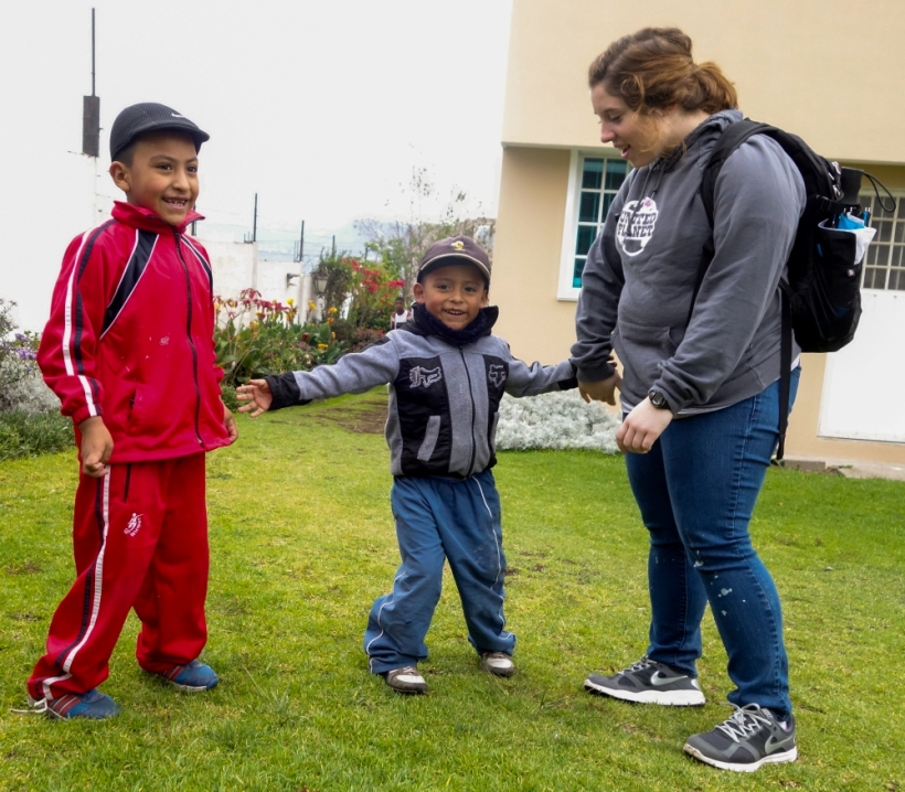 Louisiana State volunteer with two children at a daycare in Ecuador