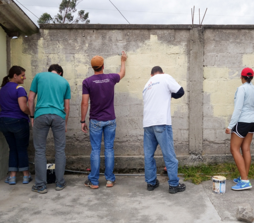 Volunteers paint a wall together