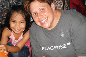 Flagstone RE volunteer smiles with child in Cambodia
