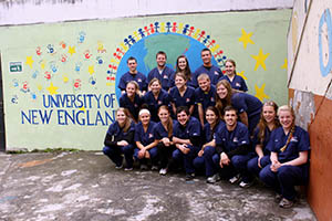 Group of UNE Dental students pose in front of mural in Ecuador