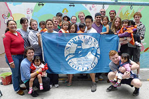 Group of student volunteers hold up Appleby College flag