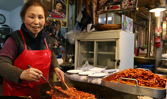 Korean woman cooks food at Tongin Market in South Korea