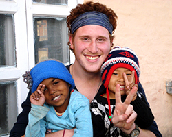 A young man and two children hold up the peace sign while smiling