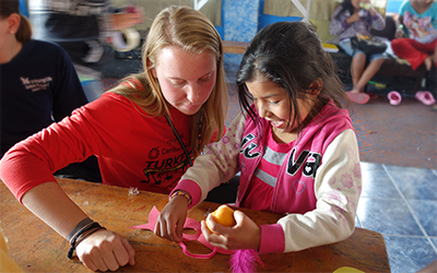 Female volunteer assists Peruvian child