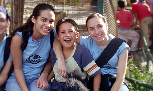 Two female United Planet volunteers with small mexican boy smile at camera