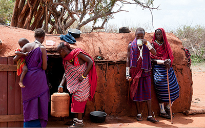 Massai villagers stand outside hut and drink tea