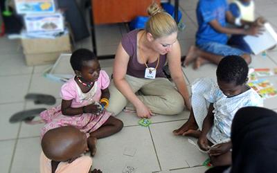 A female volunteer teaches young Tanzanian children.