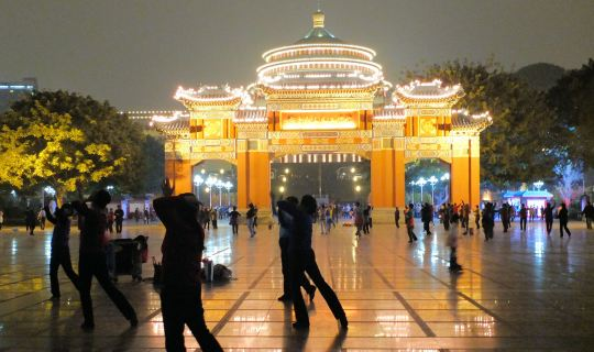 Group of people dancing at night at a dancing square in China.