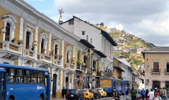 Exterior of a yellow building on a busy street in Old Town Quito.