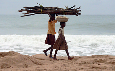 Young Ghanian children walk across beach carrying things on their heads