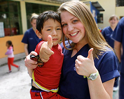 Medical volunteer and young child with thumbs up