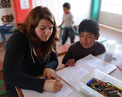 Female volunteer assisting young boy with his homework