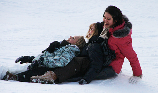 Three girls in Finland sit in snow and laugh