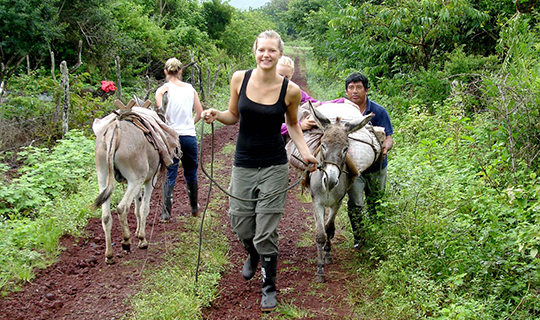 Blonde female volunteer walks towards the camera with a horse in Ecuador