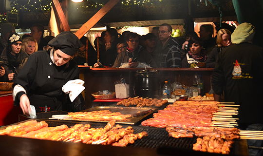 German woman cooks meat at the Cologne Christmas Market