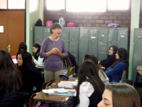 Volunteer in a purple shirt teaching a room of High School Students
