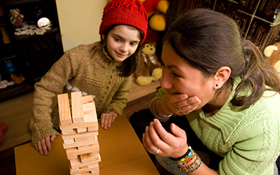 Female volunteer playing Jenga with young romanian child