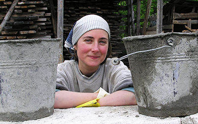 Female volunteer poses with two concrete buckets in Romania