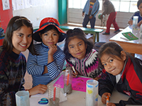 Female volunteer smiles with children at table in Peru