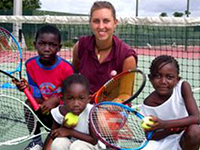 Female volunteer smiles on tennis court with children in South Africa