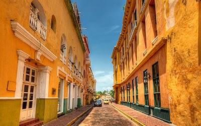 A street in Cartegna, Colombia lined with yellow houses.