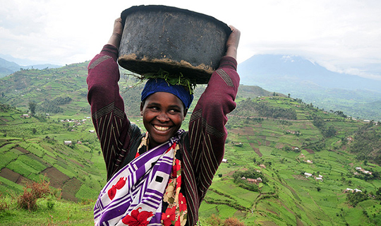 Woman holds basket on her head in Uganda