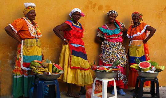 Four Colombian women dressed in traditional costumes pose infront of yellow wall