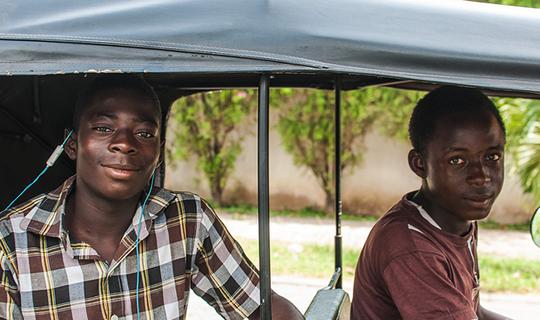 Two young men riding in a tuk-tuk in Abuja, Nigeria.