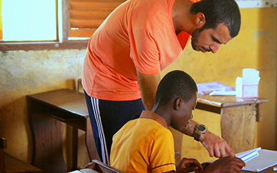 Male volunteer leans over and helps child with school work