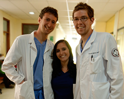 Three medical students in white lab coats smile for the camera.