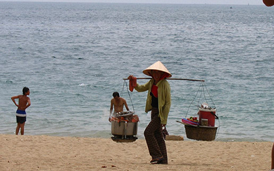 Vietnamese women walks along beach