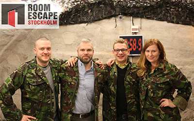 Group of people pose in front of Roomescape clock