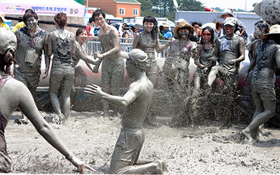 Group of Korean teenagers play in a pool of mud during the Boryeong Mud Festival, South Korea