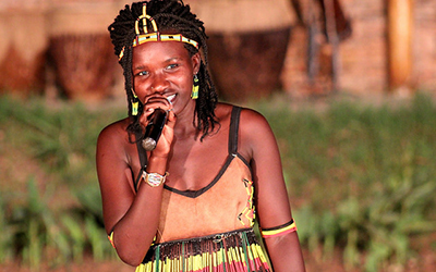 Woman holds microphone at Ndere Cultural Centre, Kampala