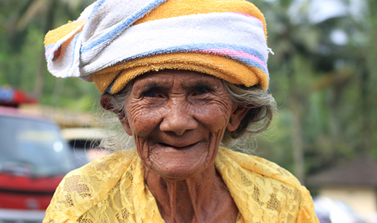 Old Indonesian woman dressed in yellow smiles at the camera