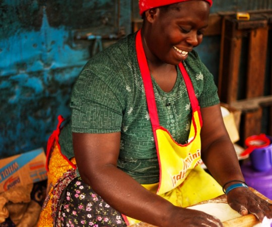 Kenyan woman rolls out dough with rolling pin