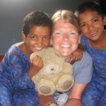 Female volunteer smiles with nepalese children