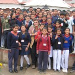 Female volunteer smiles with group of children in Nepal