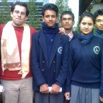 Male volunteer smiles with group of students in Nepal