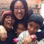 Female volunteer smiles with nepalese boys