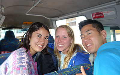 Three volunteers on a bus smile at the camera