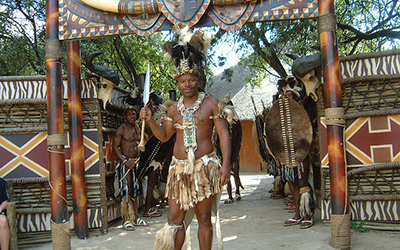 Male Zulu dancer stands outside Village near Johannesburg, South Africa