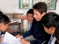 Male volunteer helping other male students with classwork