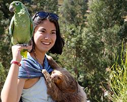 Female volunteer poses with sloth in Peru