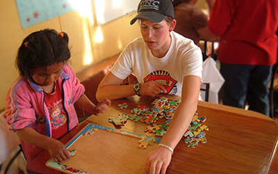 Male volunteer does a puzzle with young child